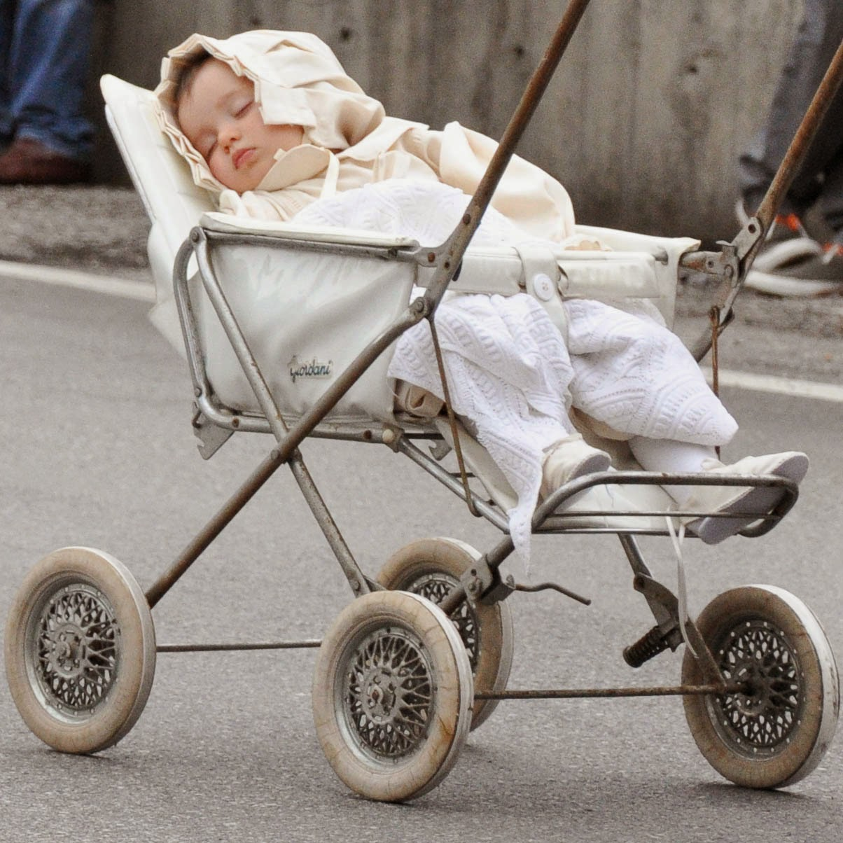 A baby in a vintage pushchair at the Parade, Donkey Race, Romano d'Ezzelino, Veneto, Italy