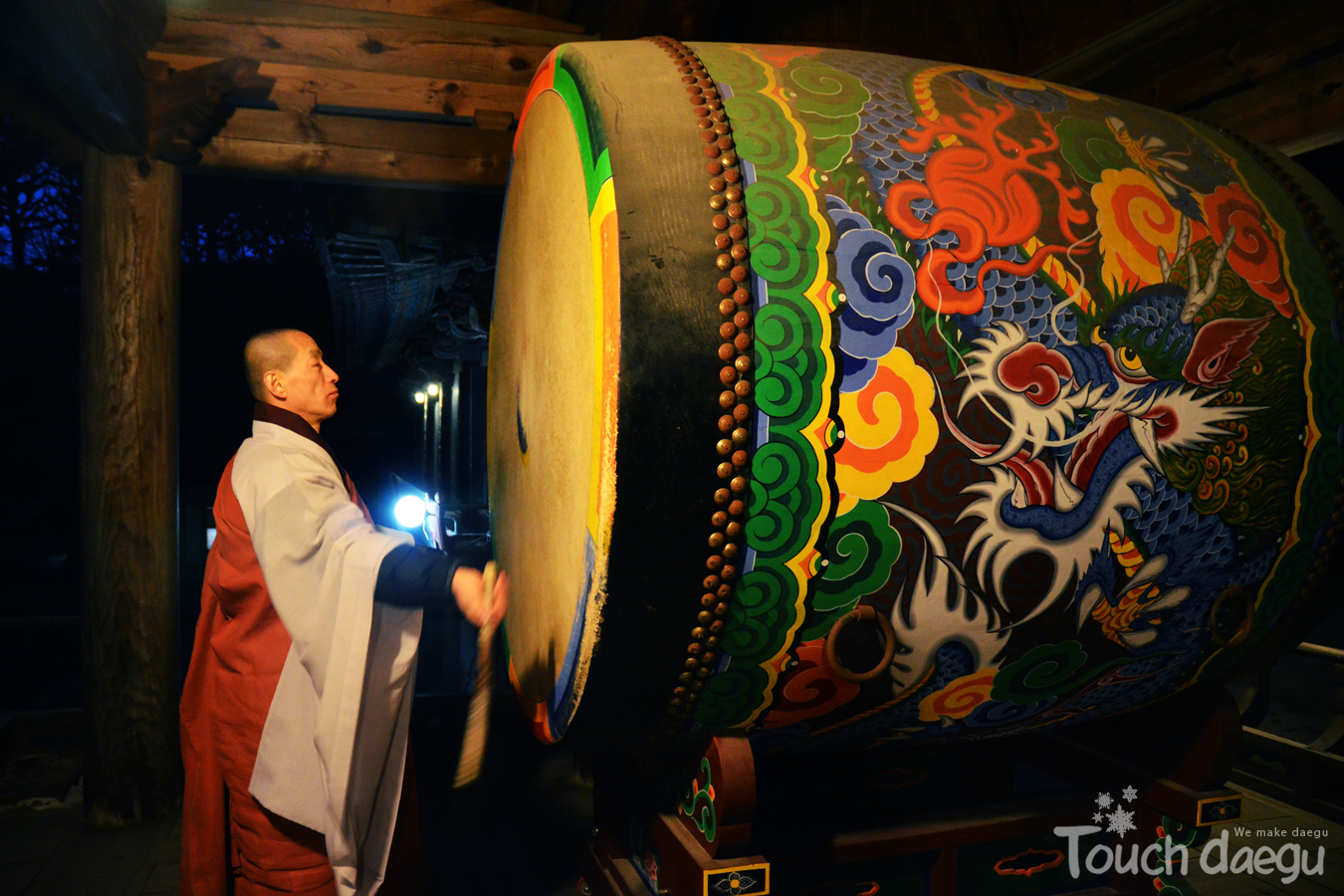 A monk is playing the drum