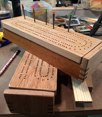 two cribbage board boxes closed with pegs in the board