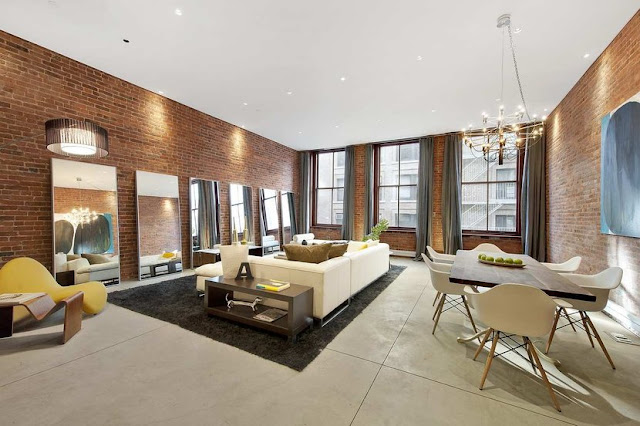 great room and dining room with exposed brick walls, high ceilings and a white sofa faces a wall of large, decorative mirrors mirrors. White eames chairs are around a large wooden table.