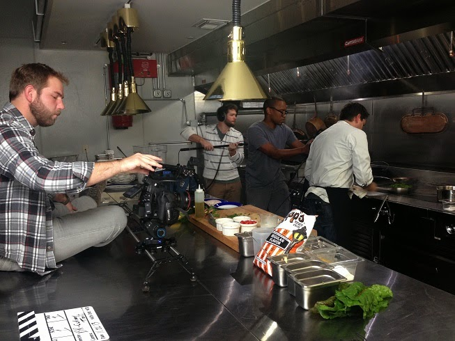 Fred Mince climbing counter tops while Jordan Lewis and Dan Jones grab some shots of Chef Jeremy Langlois in the kitchen