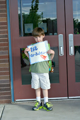 child holding cute sign for what grade he is in