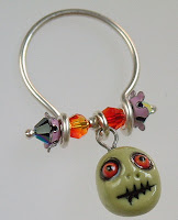A ring handmade from sterling wire with crystals and porcelain bead zombie charm.