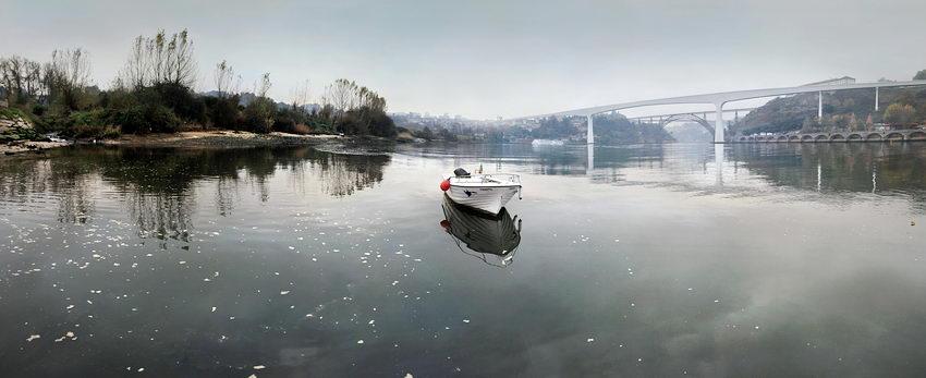 Foto panorama revelando um barco fundeado no Rio Douro em primeiro plano e três pontes ao fundo.