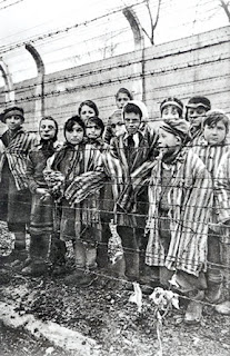 Nazi concentration camp:  Auschwitz children behind barbed wire fences
