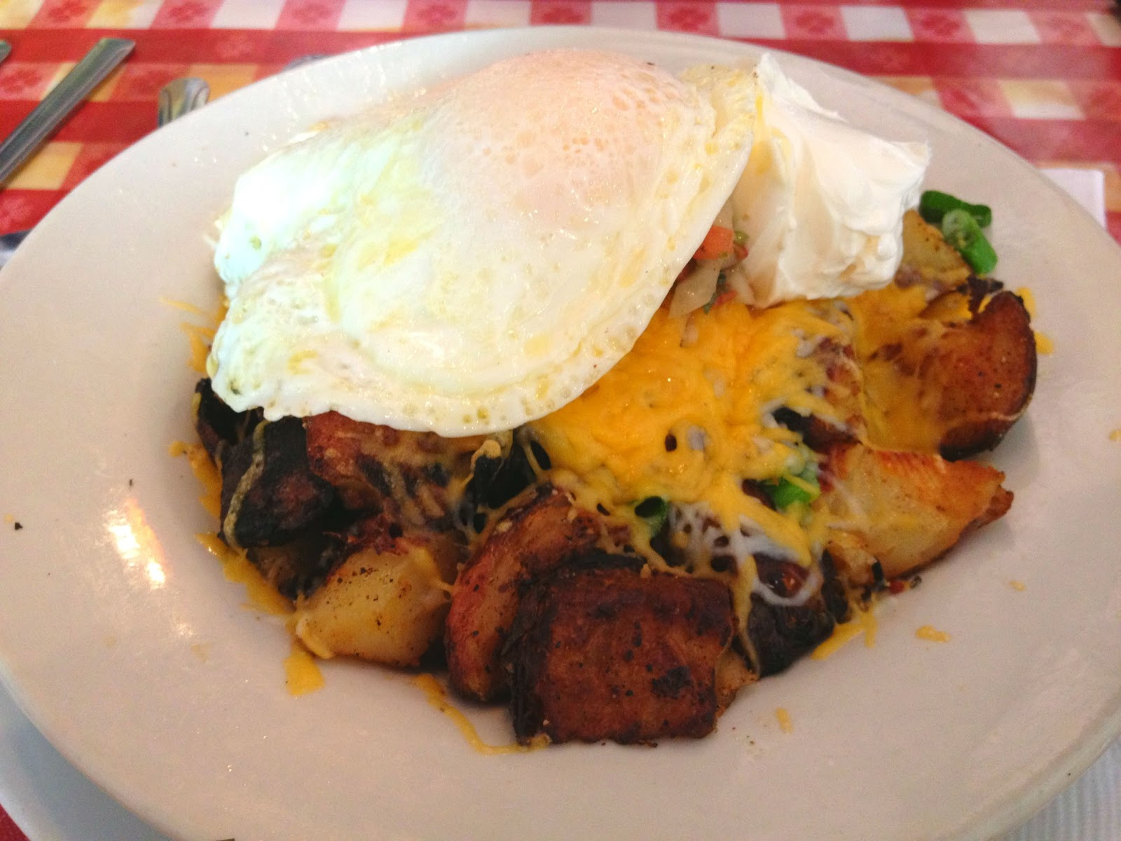 Home fries topped with cheese, bacon, salsa, and an over-easy egg with a dollop of sour cream
