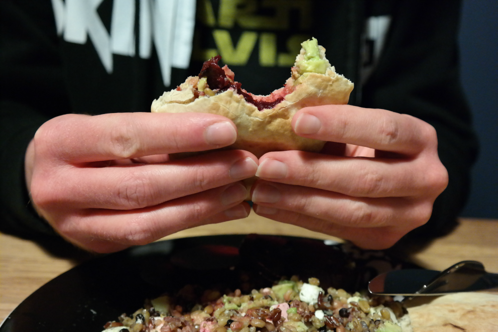 Steve's hands holding stuffed pitta bread