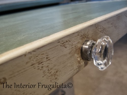 Close up of glass knob on faux secretary desk
