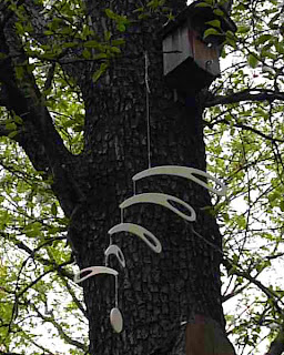 Photo of Hanging Mobile #001 in front of a tree stem