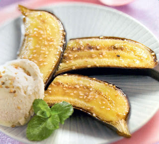 honey baked bananas with sesame seeds. Halved bananas, baked with honey, topped with sesame seeds and served with ice cream and a sprig of mint