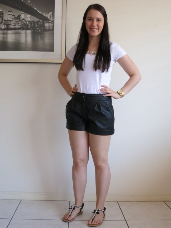 Black leather shorts, a white t-shirt with gold accessories for daytime