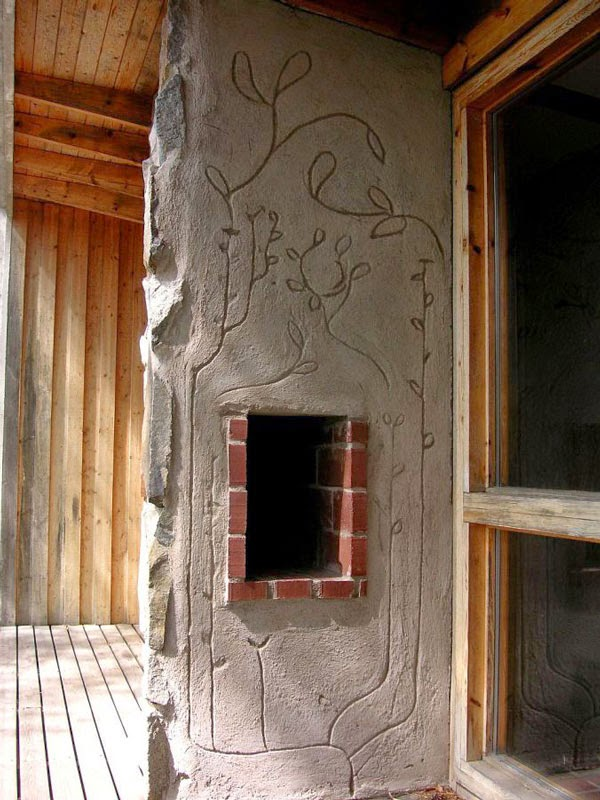 fireplace with floral design carved into cement by Ralph Erskine