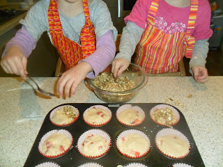 Spooning oaty topping onto Strawberry Muffins.