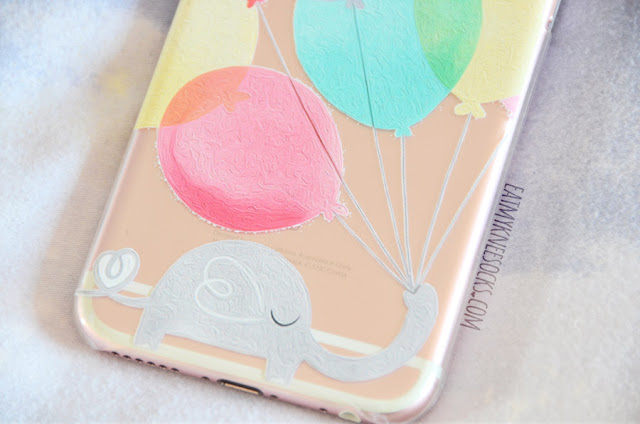 This design, made by Clash Cases, features a gray elephant holding an assortment of colorful balloons, with an interesting abstract swirled texture to the print.