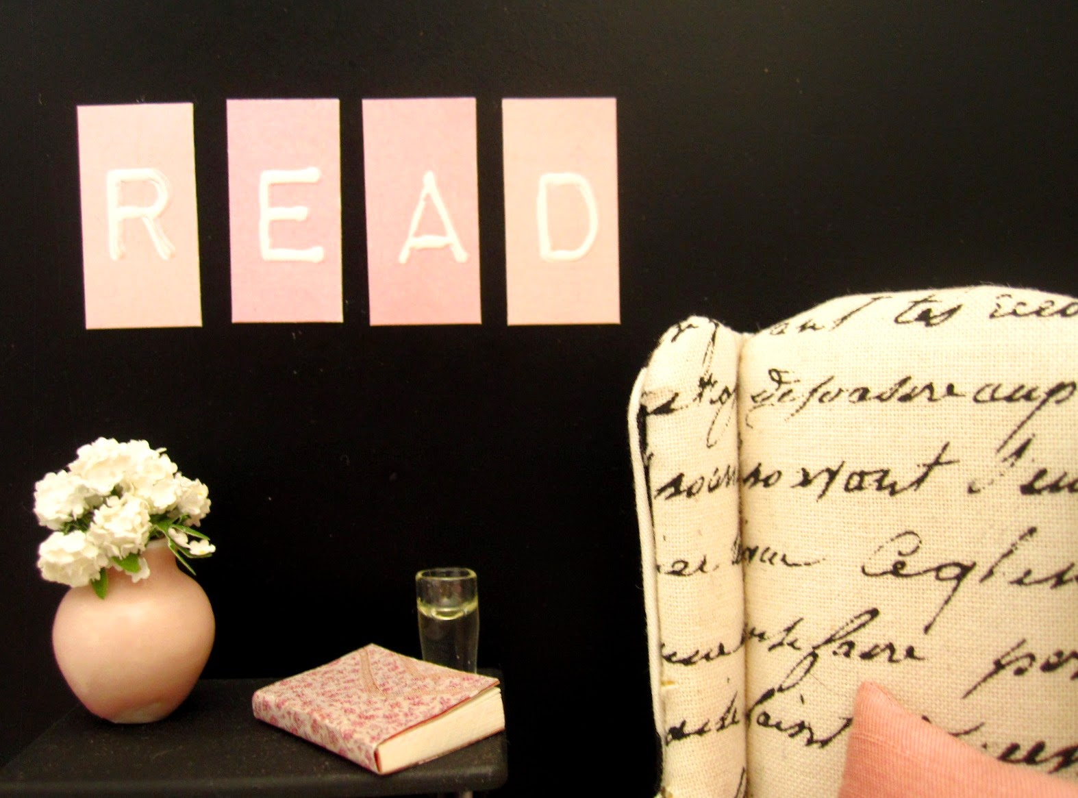 Modern doll's house miniature scene of a black and white wing chair against a black wall. On the wall are the letters R,E,A and D in pink and white and on the table under them is a pink vase with white flowers, a book and a glass of water.