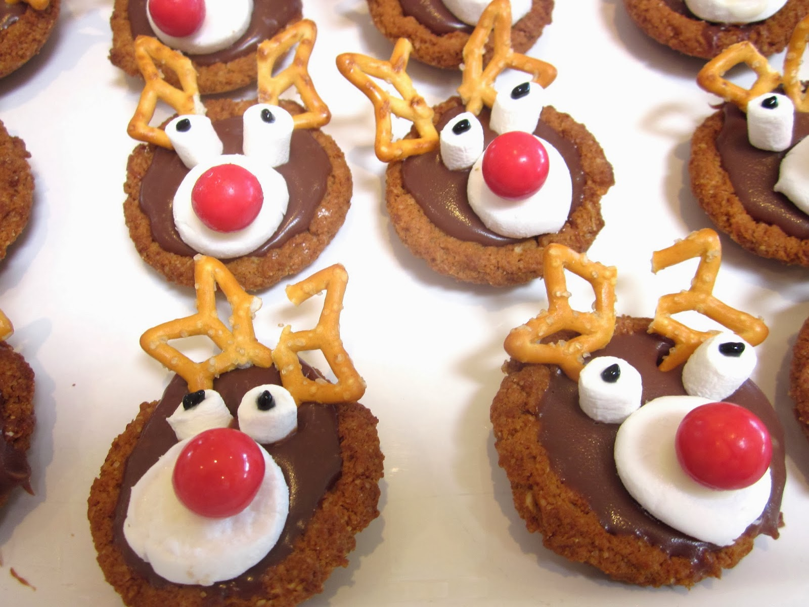 4When cookies are set but not completely dry press pretzels pieces onto cookies to create antlers 5Cut a jelly bean in half or use a candycoated chocolate candy for the nose 6To create the eyes use a white piece of candy or white decorative icing