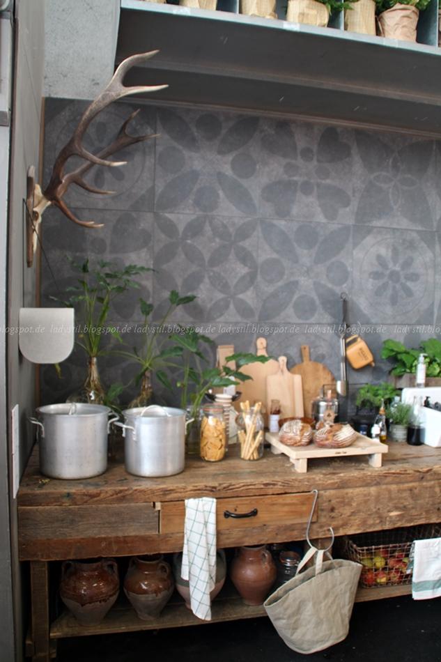 Holzküche mit grauen gemusterten Fliesen und weißen Küchenaccessoires auf der vt wonen en design beurs in Amsterdam 2015