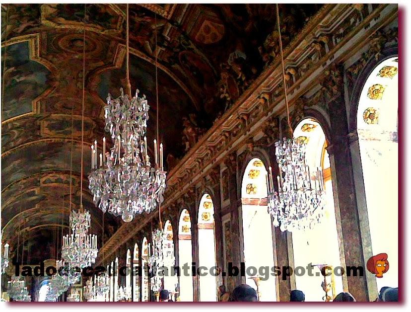 Foto com detalhe do teto, candelabros e janelas em arco da Galeria dos Espelhos do Palácio de Versailles, França