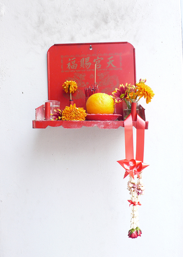 Red offering shelf with orange flowers, josh sticks and an orange.