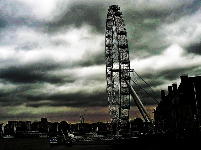 silhouette of the London Eye against a cloudy dark sky