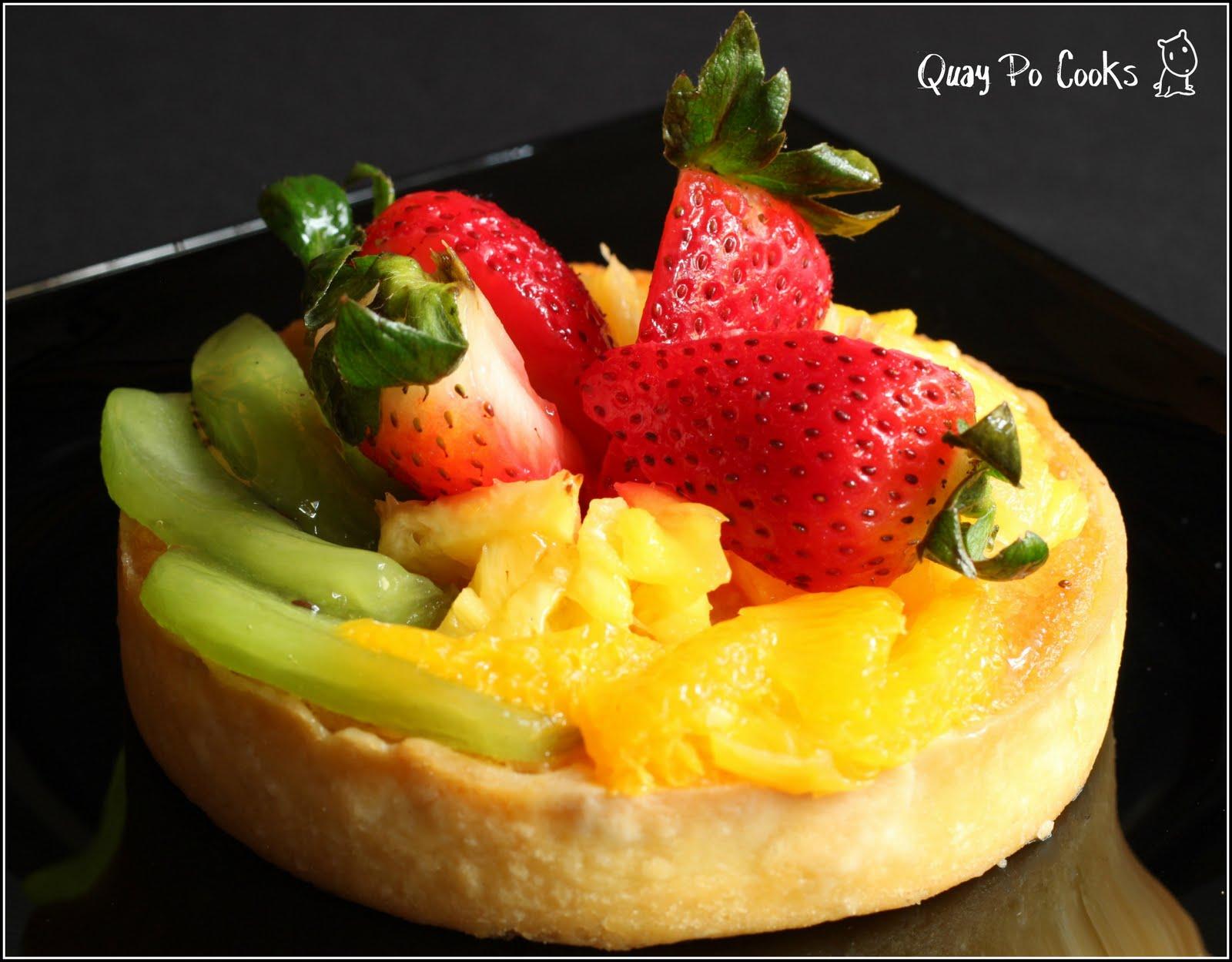 Almond cream fruit tart with orange slice, pineapple and strawberries