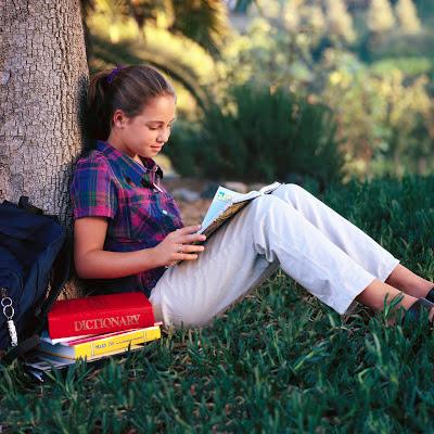 Una niña, sentada y apoyada en un árbol, leyendo un libro.