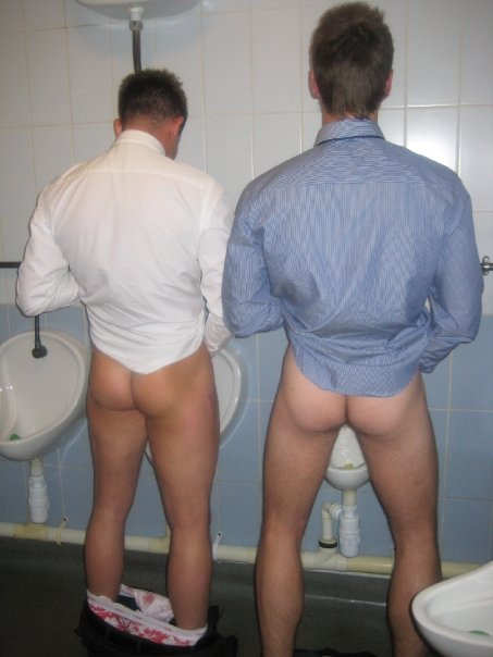 Naked guys pissing at urinal