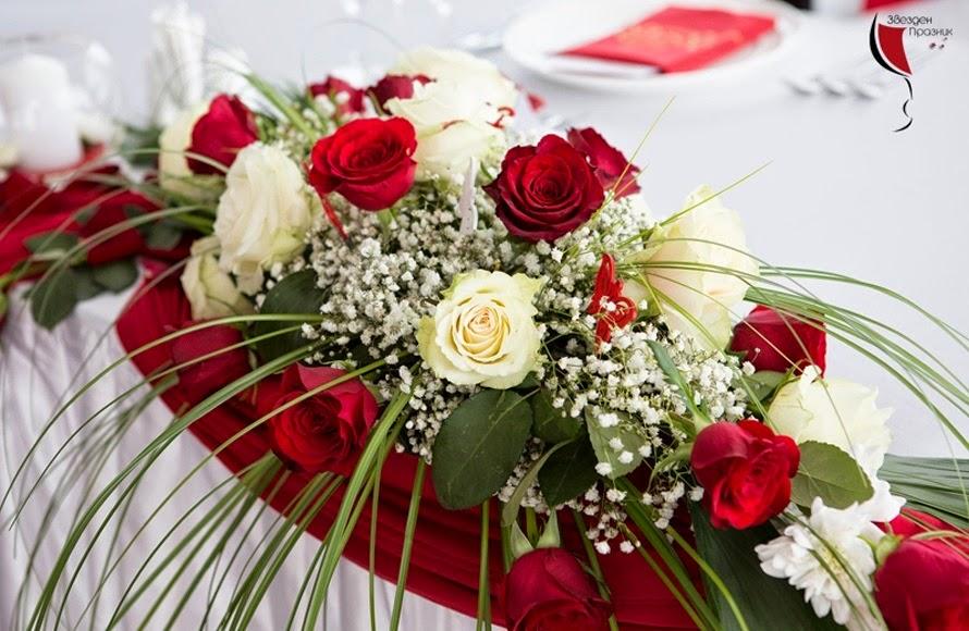 красива декорация за булчинската маса от червени и бели рози с гипсофила