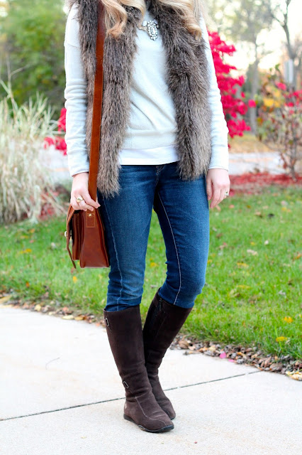 White dolman sweater, fur vest, riding boots, jeans