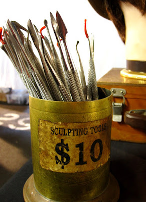 A container of sculpting tools for sale on a market stall.