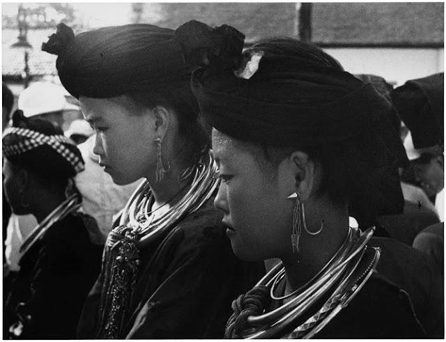 Man Cok, Indochine, 1936 ; Vue de profil de deux femmes de l'ethnie Man Coc en tenue traditionnelle, portant un turban, des boucles d'oreilles et de lourds colliers, lors d'un rassemblement
