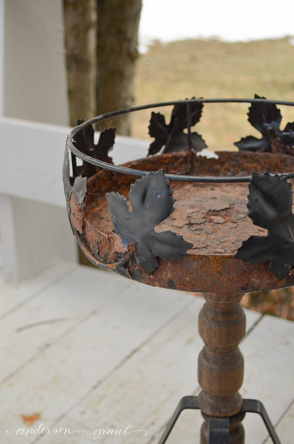 A rusty plant stand repurposed and painted to create an outdoor accent table for your deck. |  www.andersonandgrant.com