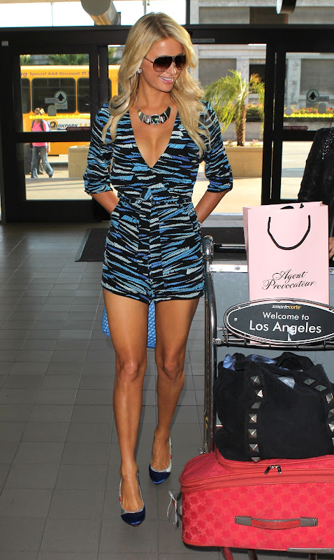 Paris Hilton standids beside her bags at LAX Airport