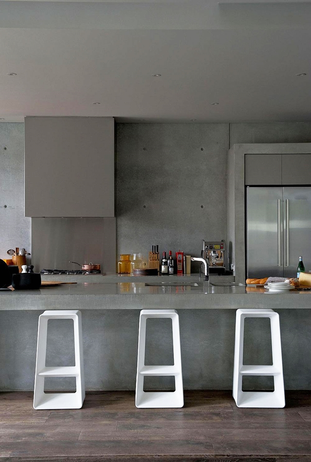 Concrete kitchen island with three white chairs
