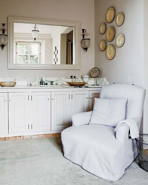 mueble blanco de lavabo y sillón en el baño