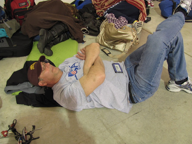 An older man sleeps on the floor
