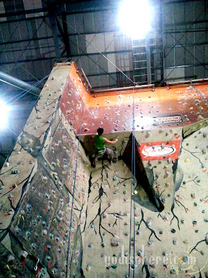 Wall climber climbing a difficult overhead portion of the climbing wall