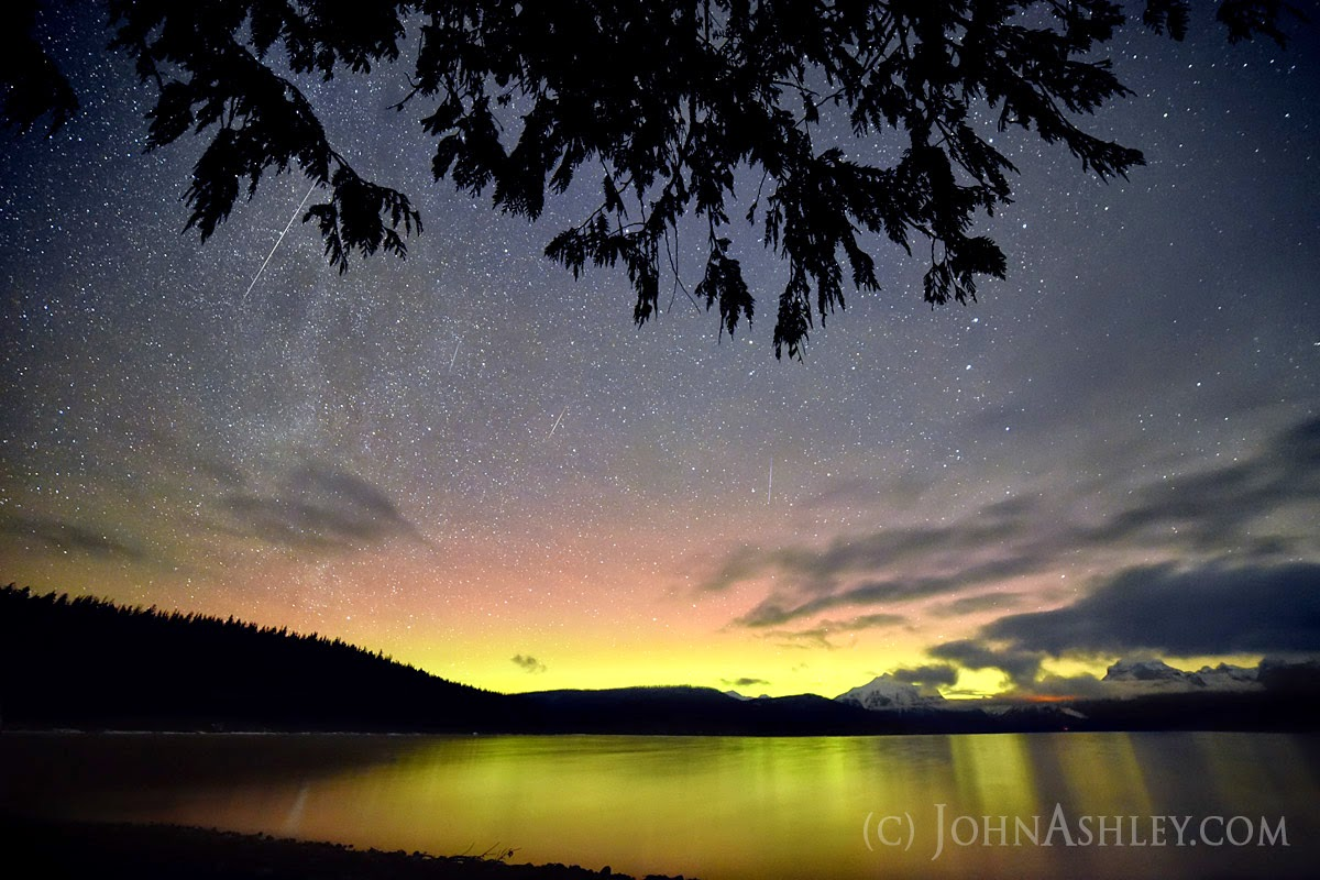 Four Geminid meteors slice through the sky above weak northern lights, viewed over Lake McDonald, in Glacier Park early Monday morning (c) John Ashley