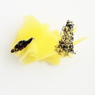 A yellow washing-up sponge which has been cut into small pieces and rearranged and then sewn back together in an abstract form.