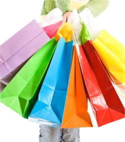 main de femme qui tient des sacs de courses de toutes les couleurs
