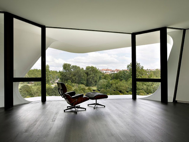 Brown Soft Chair and Big Window Wall which is Made from Glass Material