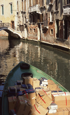 boxes in green boat floating down Venetian canal.