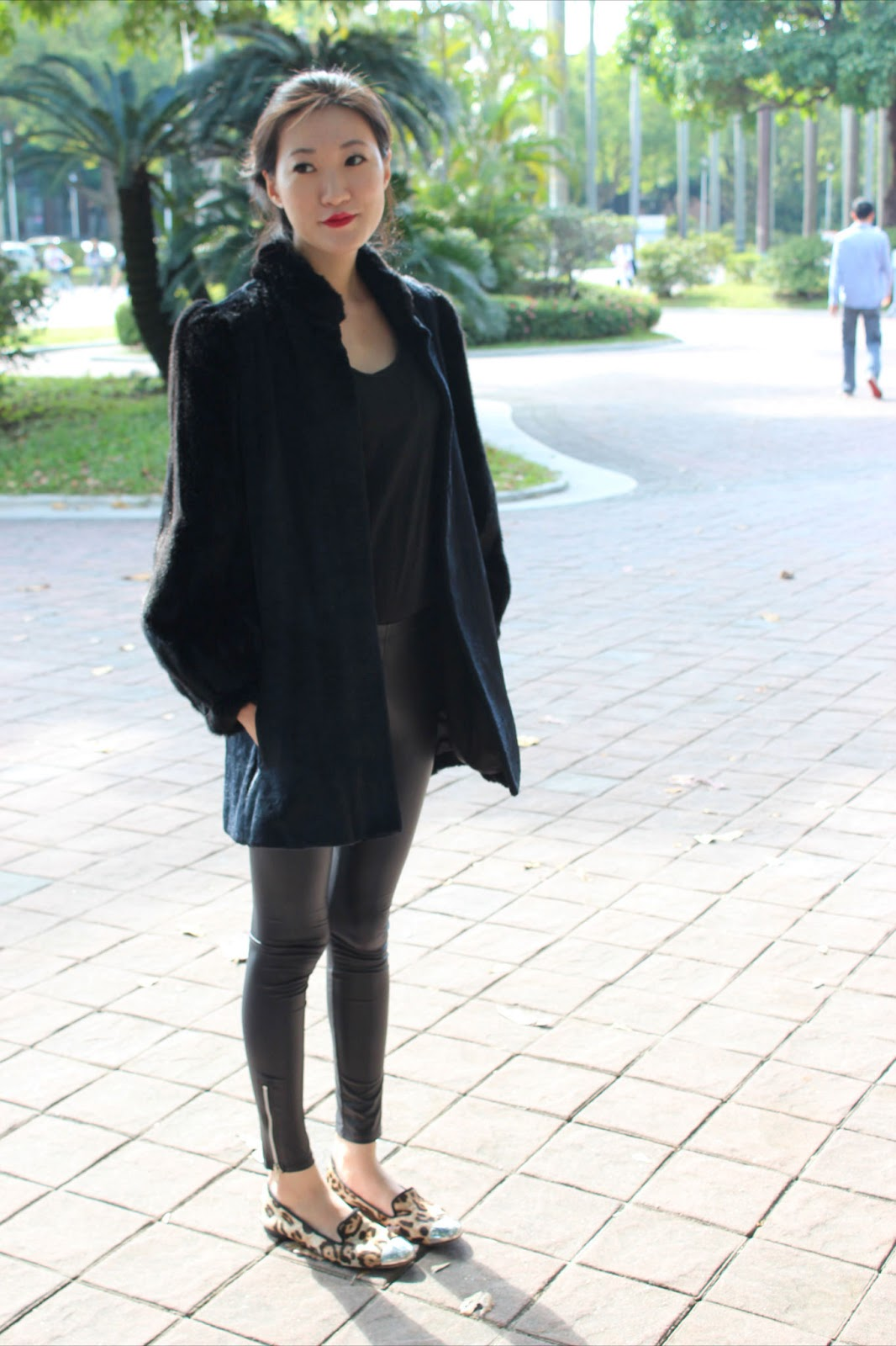 National Taiwan University Student wears a black felt coat with black zippered leather leggings and animal print slippers slip-ons flats with a metallic tip