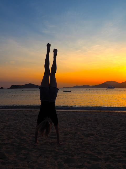 Silhouette of a girl doing a handstand against the sunset and ocean on Repulse Bay Beach, Hong Kong