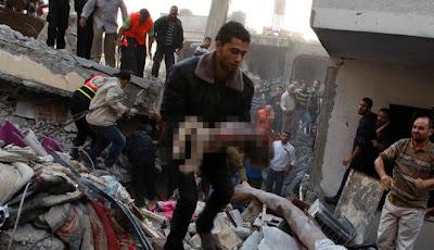 seorang pemuda mengankat jenazah seorang bayi yang tewas akibat serangan udara israel