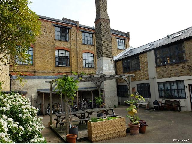 salon de jardin blanc table bois cour résidence Londres Dalston ancien bâtiement industriel cheminée usine