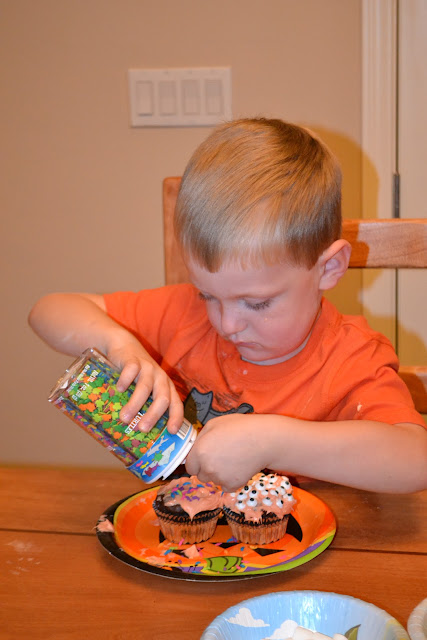 Carter decorating Halloween cupcakes