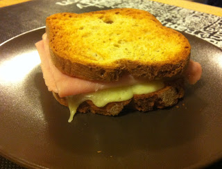 Ham and gooey cheese sandwich on a brown plate.