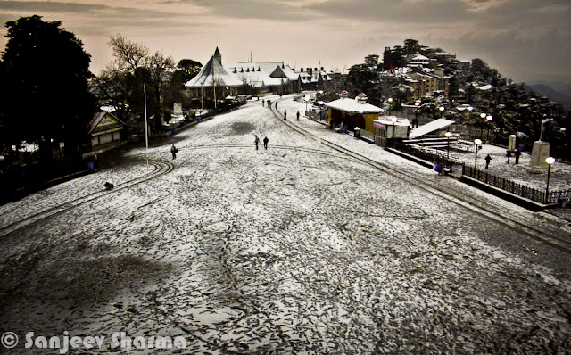 Shimla has been getting snowfall since 5th January 2012 and Sajeev has been capturing each moment of post-snowfall moments at various places around Shimla - Mall Road, Ridge ground, Scandal point, Lakkar Bazar etc. This year Shimla is getting heavy snowfall and some of the evidences can be seen in this Photo Journey from last week... Sanjeev Sharma with unknown Cameraman, Zee news, Shimla :)Sanjeev himself on Ridge Ground, while it's snowing on Ridge Ground, Shimla, Himachal Pradesh, India. You can see Christ Church on one corner of the Ridge and Shimla Library adjacent to it. Somehow Shimla is known by these two buildings. Yesterday only I saw fridge magnet at Connaught Place, Delhi with these two buildings carved on a marble piece to make a souvenir of Shimla, Himachal Pradesh. There were lot of other stuff form various cities of India like Jaipur, Varanasi, Maisoore etc.Here is a photograph with footmarks of people who were enjoying fresh snowfall on Ridge Ground and left for their homes.Although there are still few folks roaming around. Whole sky is covered with dense mist or clouds. The leading path is actually touching Mall Road, which is one of the main places people love to roam around in Shimla. buildings on left side are Goofa Restaurant and Bar by HPTDC and Gaitey Theatre, which was renovated last year only.Here is a closer look to Goofa Restaurant and Bar. One of the decent place to have dinner on Ridge Ground, although our experience of Goofa bar was not so good, when we were in University. But this is considered one of the decent places..Business in Snow... The famous Krishna bakers is closed but 100 Pipers and other brands of whiskey are available. And probably Rum would be more demand in such a lovely snow. Just notice the height of snow on the road... All these shops are located on lower part of the Mall Road...Another view of ridge Ground from an elevated boundary which leads towards Jakhu Temple, Shimla.Snow was on and off during last 10 days and yesterday there was heavy snowfall, which made people comment negatively about it. Till yesterday everyone from Shimla was putting happy and interesting statuses about Snowfall on facebook. But suddenly things changed yesterday when this snow started impacting lives of people in Shimla. For tourists, heavy snowfall can be good but for loacl folks it creates lot of problems at times. Water and Electricity supply is one of the main challenge during heavy snowfall hours. Notice the forest behind Mr. Sanjeev which are still white and these high deodars look amazing with snow on top of themPath created by Ambulance is being smartly used by these folks. vehicles are not allowed on Ridge Ground and Mall Roads.. Only Ambulance or police vehicles are allowed as and when required. Although many bollywood movies have shown vehicles flying on ridge ground. All that is done after special permissions from Shimla Authorities.Here is a a view of Shimla Ice Skating Club, which is located just below Lakkar Bazar, Shimla. This club is also visible from top of Indira Market on Ridge Ground. During December a national level event is organized, where lot of professionals come to this club for showing their Ice Skating performances. Even without ice these folks from Shimla can be seen on Mall Road and Ridge on  every Saturday :)Evening view of Ridge with spoiled snow... Place like Shimla are enjoyable either during fresh snowfall or without any snow. After 2 or 3 days of snowfall, snow melts or take a shape of huge pieces of ice which are risky to walk and dirty as well. During that time, snow in places are Kufri or Narkanda is more enjoyable. In fact, these days Skiing training is going on at Dhomri, Narkanda...Mr. Sanjeev, covered with multi-layered cloths and posing for a photograph against scandal point. Scandal point is a place from where two roads are diverted - one towards Ridge ground and other continues as Mall Road towards Shimla Town Hall and Gaiety Theatre.Gukli just stood up for this photograph, otherwise he must be busy in making snowman or playing snowballs :) ... Smile on his face is telling about the excitement about fresh snowfall in Shimla.Every year tourists come to Shimla during last week of Decemeber in a hope of Snowfall, but now timings have shifted a bit. For last few years, Shimla is getting snowfall in second week of January or towards end of first week.This year (2012), it was first time that some of the regions in Himachal got snowfall. Places like Hamirpur were also covered with white sheet of snow, although it remained only for few hours and then disappeared. At the same time various places of Kangra District got snowfall - Nagrota, Palampur, Dharmshala and Kangra town itself. Kangra Twon got snowfall after 52 years...Sanjeev is still waiting for his car to be uncovered of Snow Blanket... Try to imagine, how people in Shimla must be commuting to their offices and other places for some work... Conditions get worse in case of continuous snowfall for longer period of time.Many businessmen in Shimla make more money during tis season but at the same time, many folks with small setups loose lot of business due to heavy snow. I am sure that every weekend Shimla is getting lot of tourists from Punjab and Delhi...Sanjeev in perfect pose for this photograph with snow in the background :) (Shimla, Himachal Pradesh, India)Another amazing view of Ridge Ground covered with Snow and few folks walking on it... I still remember the day when I saw snowfall first time and we came to Mall Road for playing with snowballs... Everyone from our class was on Mall Road and whole day was full of fun and enjoyment....Sanjeev looks pretty happy and hopeful about this snowfall... Probably he is done with his walk on Mall Road and moving towards Press Club at Indira Market on Ridge ground of Shimla TownHere is last and wonderful photograph of this amazing Photo Journey by Sanjeev Sharma. Hope that snowfall comes with happiness and keep whole environment cheerful without any damage to anyone. And if you are amongst ones who have never seen snowfall, this is right time to plan your trip to Shimla and enjoy it.Thanks a Lot Sanjeev Sharma for such a Lovely Photo Journey with full of life photographs from last one week.