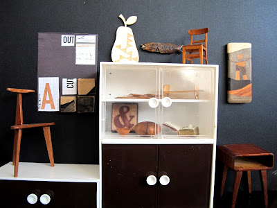 Modern dolls' house miniature display wall in a gallery. A collage art work is hanging on a black wall. In front of it is an art chair. On the left is a cabinet  with a wooden pear, fish and chair on top of it, and a table and wooden art work next to it. In the cabinet are a selection of items including a wooden ampersand tile, a modern tray, wooden bowls and a book safe.